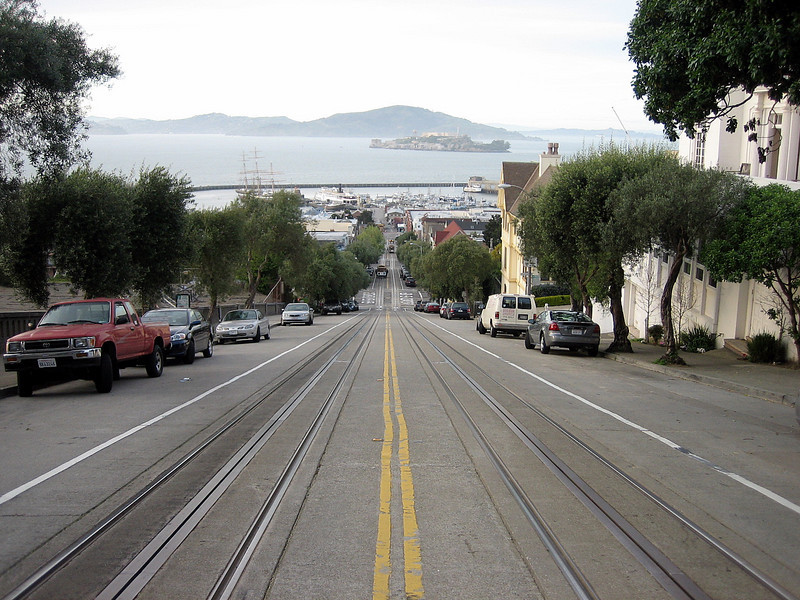 This is by far the steepest main street gradient I have ever walked <strong>UP</strong>  TIP: If you ever decide to walk the same route, the I recommend you tackle Hyde Street from the south (going north). It's downhill all the way .. which is a much better direction, especially if you go by Shanks's Pony!  [Notice Alcatraz Island in the background.]  ----------------------  <strong>Wednesday, March-20</strong>  Around noon today we decide to return, again via the Cal-Train service, to San Mateo and collect the STeed from the local Honda workshop. 864 dollars poorer we're riding back up to Skyline Boulevard and await the oncoming evening's activities. Because tonight we finally meet-up with my far-away friends ..