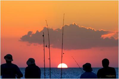 Fisherman and a descending golden sun