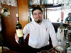 """OAT Patagonia trip, Dec 2013.<br /> This portion of the tour took place on the Via Australis boat.<br /> One of the bartenders holing a bottle of """"Carmenere"""" wine."""
