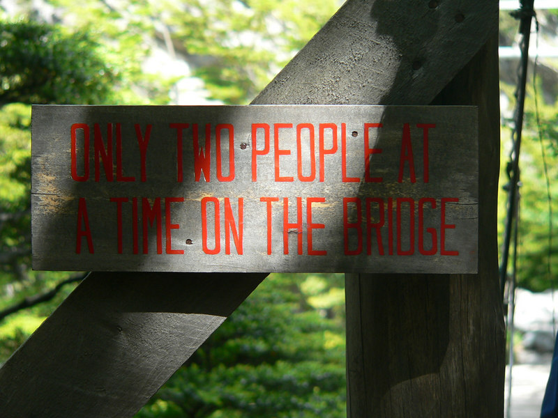 "it reads ""ONLY TWO PEOPLE AT A TIME ON THE BRIDGE"""