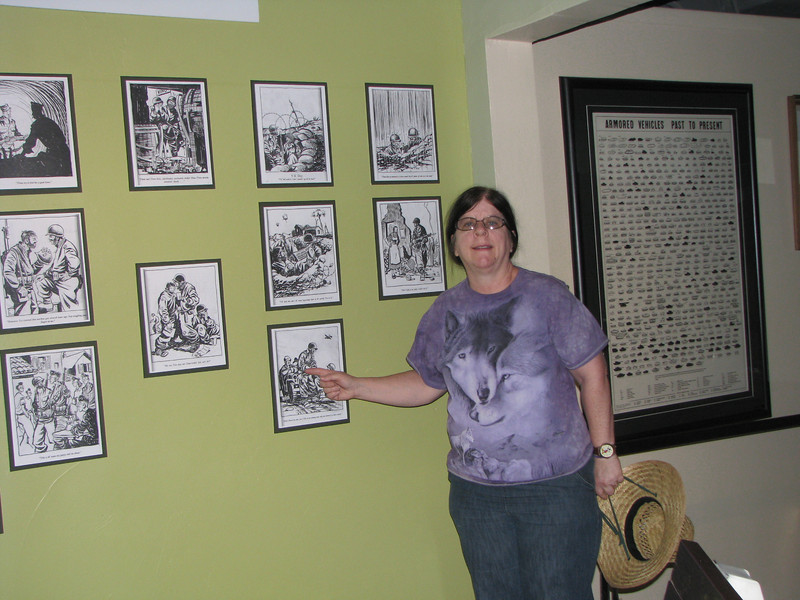 Julie in front of a wall of political cartoons.