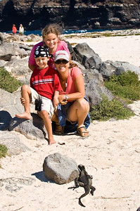 Family, posing for a Marine Iguana, Galapagos Islands, Ecuador.
