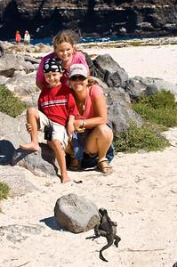 Family, posing for a Marine Iguana, Galapagos Islands, Ecuador.