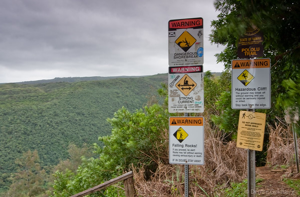 Warning signs at the top of a very steep trail leading down to Polulu Beach.