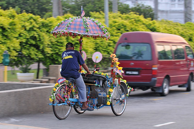 "Tricycle. Penang (pronounced /pəˈnæŋ/; (Malay: Pulau Pinang)) is a state in Malaysia which is located on the north-west coast of Peninsular Malaysia by the Strait of Malacca. The name ""Penang"" comes from the modern Malay name Pulau Pinang, which means island of the betel nut tree. It is the second smallest state in Malaysia. Penang is often known as ""The Pearl of the Orient"" and ""Pulau Pinang Pulau Mutiara"" (Penang Island of Pearls)."