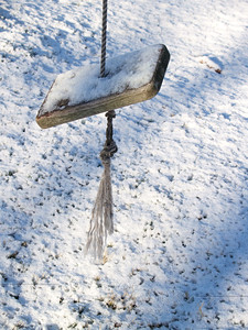 Old weathered swing after winter snowstorm; morning light