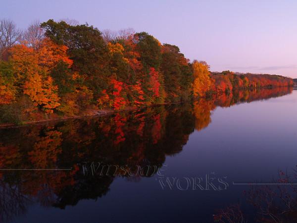 Brilliant fall color reflected in Lake Nockamixon at dusk