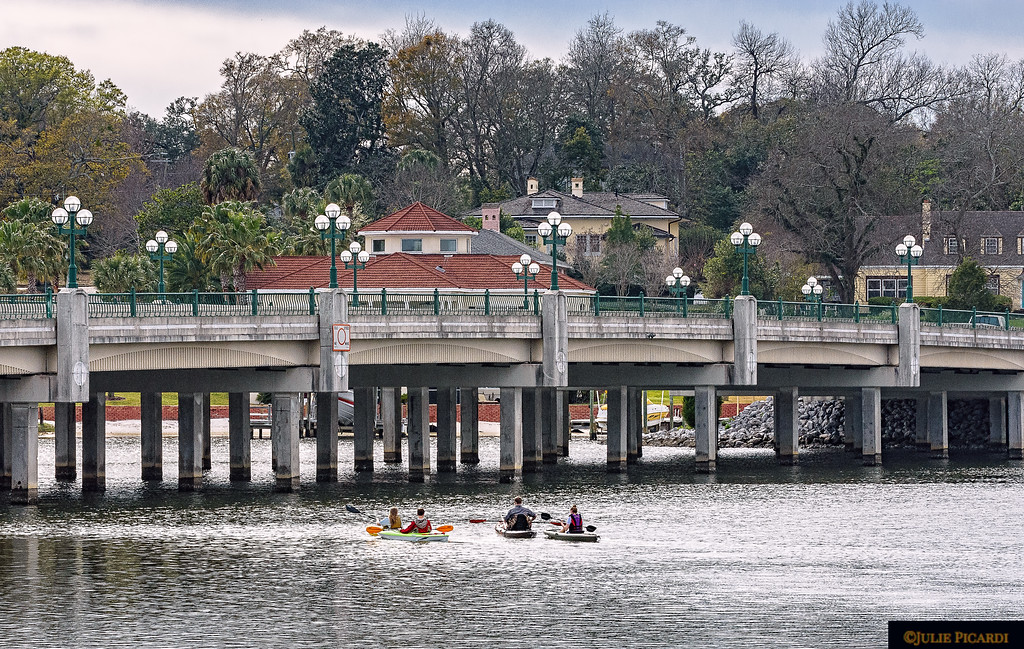 Kayakers paddle their way under the Bayou Texar bridge.
