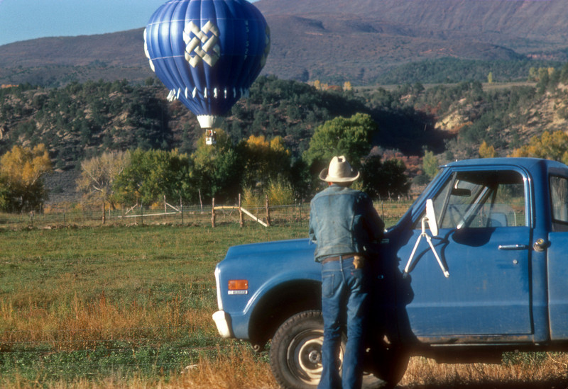 Cowboy watches as a hot air ballon sails in over the pasture.