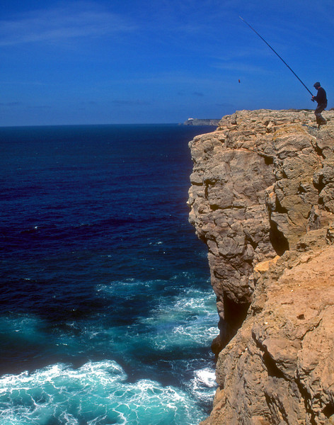 The fishermen of Sagres have devised a method of lowering a basket on a heavy line. The hooked fish swims into the basket in the water to hide and is hauled up.