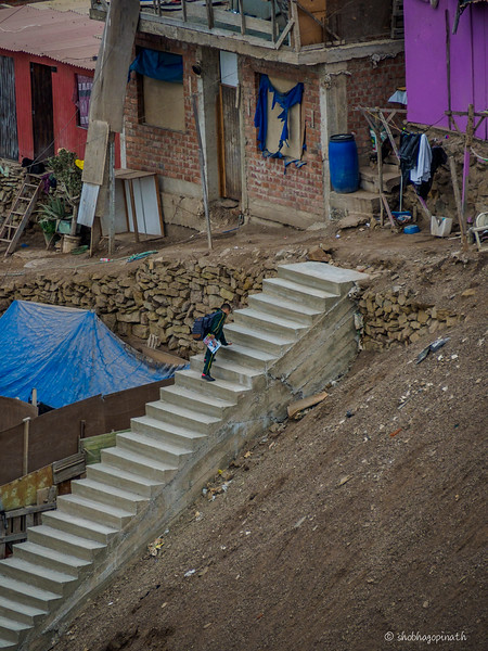 Boy walks up an uncompleted stairway to his home in teh shanty town