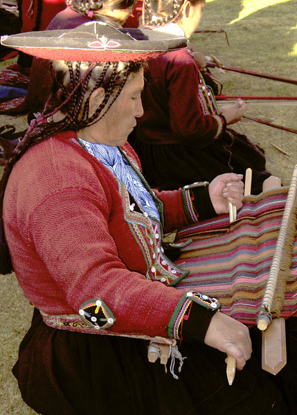 Weavers in traditional garb weaving on hand looms at the Chinchero, Peru textile center