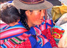 Beautiful face of mother holding child at the Market of Pisac, Peru