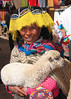 Girl with lamb for sale at market, Pisac, Peru