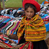 Serious little merchant with woven handicrafts.