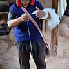 Peruvian man demonstrates the old Inca way of spinning wool into thread.