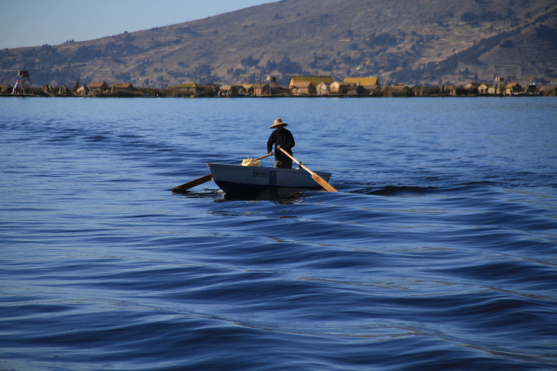 A Uros native cruising by our boat.