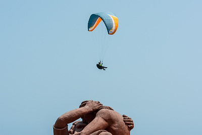 """A paraglider hovering over the statue """"El Beso"""" (The Kiss) in Love Park."""