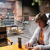 Kathy eating an empanada in the Pisac market that was cooked by the guy behind her