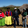 (Photo 0850)  Julie and our local tour guide Charo with the locals from the floating village in Puno, Peru.
