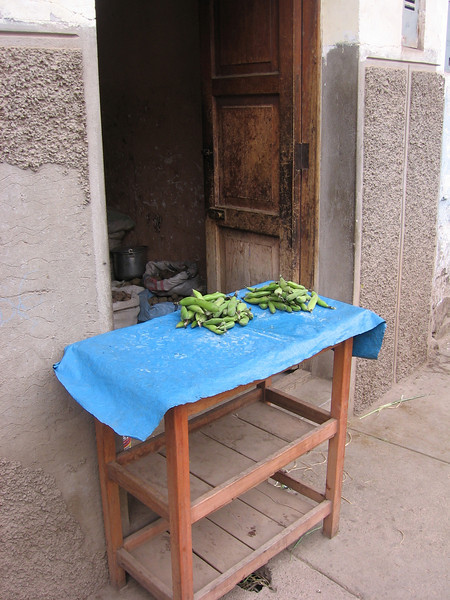 Plantains on a table; not sure if they were for sale or just getting some air...  You can also see sacks of potatos just inside the doorway.