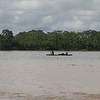 Boatmen on the Maranon, near the start of the Amazon River.  A pink dolphin surfaces between us and them, top fin just barely breaking the top of the water to show its rose-colored back