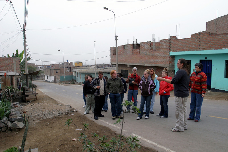 Valerie Paz Soldan talks to student in her Peru course during a tour of the Pampas community, a shantytown in southern Lima
