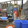 Typical open-air room: a variety of materials for building supplies, glass containers dug from trash awaiting transport to a facility where the deposit on glass may be obtained, and a variety of containers to hold water from a community tap or water bladder.  Water is not available within individual homes unless by delivery by a water truck or taken during limited availability hours from a community tap... which may be very far away from the home.