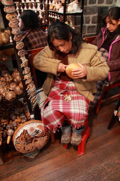 Cusco 5116<br /> Vender carving inca designs on a bowl.