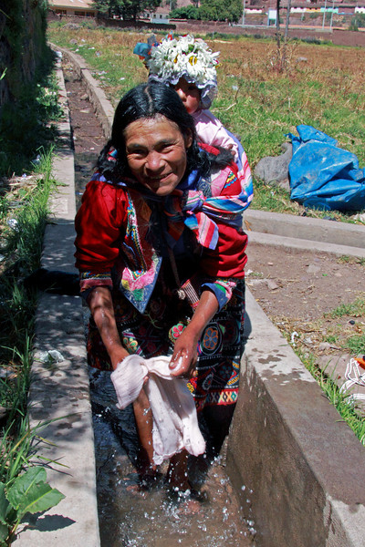 Pisac 4045<br /> Woman doing laundry in a canal in Pisac with baby on her back.