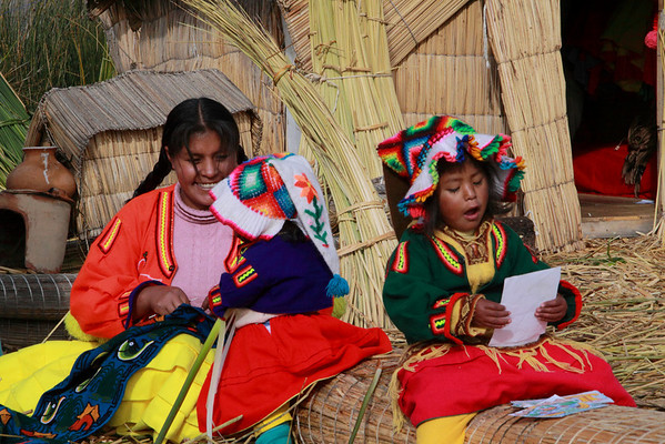 Titicaca 5659<br /> Uros mother and kids sitting on a bundle of Totora reeds on a floating island in Lake Titicaca.