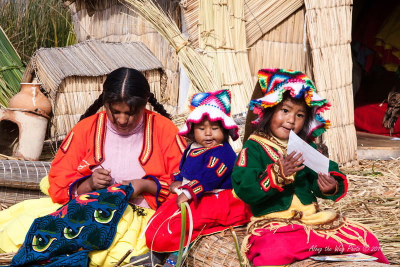 Titicaca 5662<br /> Mom and kids sitting on a bundle of reeds on a Uros Island on Lake Titicaca.