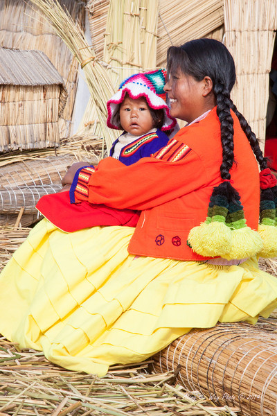 Titicaca 5649<br /> Mother with little girl sitting on a bundle of reeds on a Uros Island on Lake Titicaca.