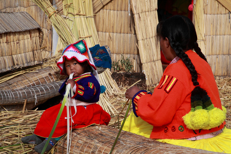 Titicaca 5658<br /> Little girl eating the root of a totora reed. The roots are also known as a water banana. You peel the top part back and can eat it. Not much taste to it, but filling.