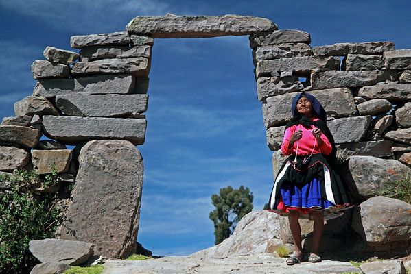 Titicaca 5368<br /> Old lady by archway on the Port Alsuno trail on Taquile Island hand spinning wool.