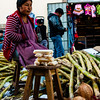 A sugar cane merchant waits for a customer in the busy Cusco market.