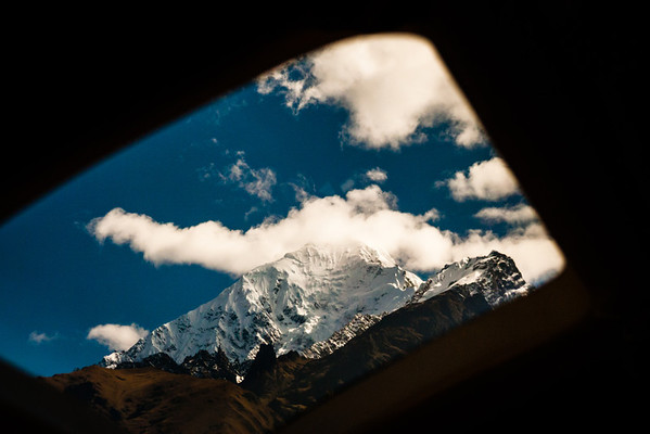The train from Cusco to Machu Picchu winds between towering snow capped mountains.