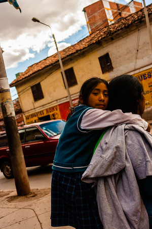 A girl waits with her mom at a bus stop after school.