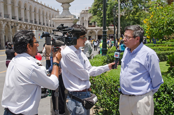 While protesters still walk the streets, a man on Plaza de Armas is questioned by ATV sur, a local TV station, Arequipa, Peru