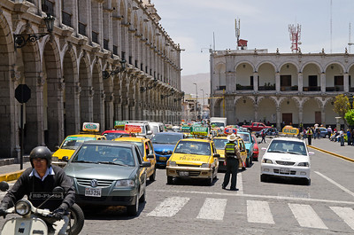 Heavy traffic, mainly taxi cabs, squeezes through the Plaza de Armas in Arequipa, Peru