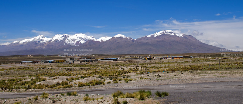 A small village in front of a snow-capped volcanic mountain range in the high plains of Pampa Canahuas National Reserve near Arequipa, Peru.