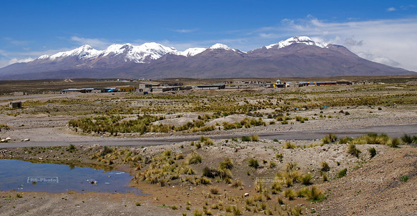 A small village in front of a volcanic mountain range in the high plains of Pampa Canahuas National Reserve near Arequipa, Peru.