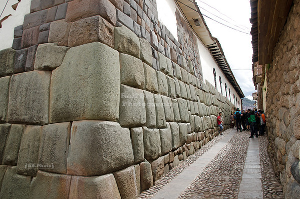 Impressive Inca masonry in Calle Hatunrumiyoc, a pedestrian cobblestone street in Cusco, Peru. The ancient Inca walls still build the foundation for many modern buildings. And like always, a hige crowd is gathering at the place where the famous 12-sided stone can be found