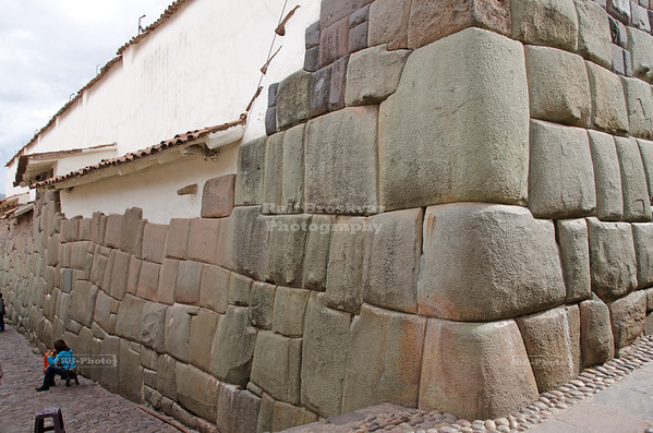 Impressive Inca masonry in Calle Hatunrumiyoc, a pedestrian cobblestone street in Cusco, Peru. The ancient Inca walls still build the foundation for many modern buildings.
