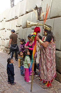 A man dressed op as Inca, poses in front of the famous 12-angled stone in Calle Hatunrumiyoc, Cusco, Peru