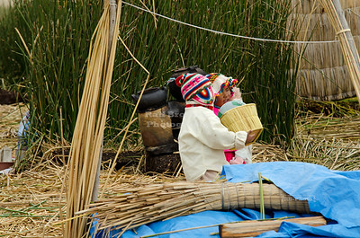 Little Uros boy and girl on Lake Titicaca setting up their shop to sell to the tourists