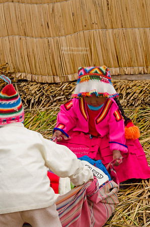 Little boy and girl on the floating islands of the Uros in Lake Titicaca, Peru