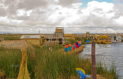 Indigenous Uros people on floating islands in Lake Titicaca waiting for the tourist boats to dock, Peru