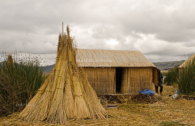 Stacked reed bundles in front of a reed house on the floating islands of the Uros people, Lake Titicaca, Peru