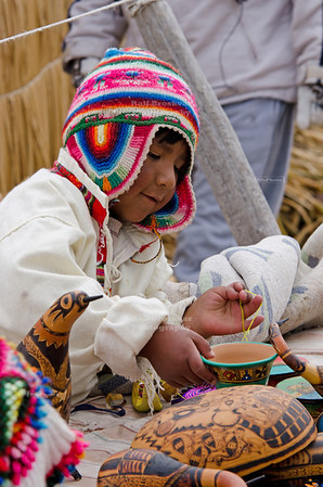 Little Uros boy im traditional clothes with hand crafted pottery on the Floating Islands of the Uros, Lake Titicaca, Peru